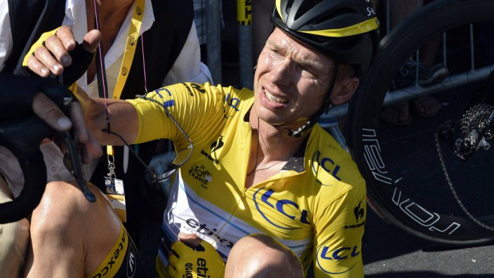 Etixx-Quick Step rider Martin of Germany, race leader's yellow jersey, is helped after a crash during the 6th stage of the 102nd Tour de France cycling race