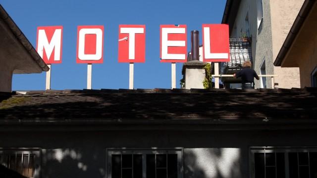 Motel-Schild auf einem Gebäude am Pasinger MarienplatzGabi Blum weist mit einer kulissenartigen Motelfassade, die eine Bautafel persiflieren soll, auf die fragwürdige Planungswut in den Stadträumen hin