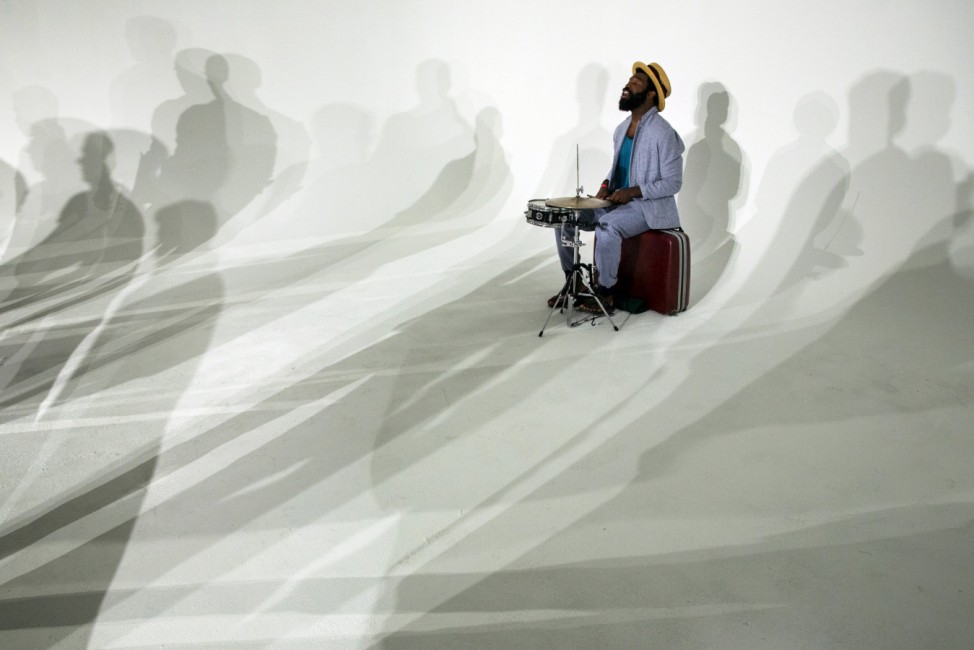 A drummer performs amongst the shadows of models at the Cadet presentation during Men's Fashion Week, in New York