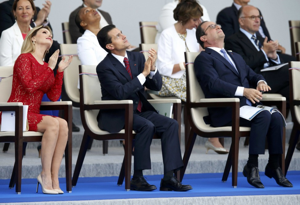French President Francois Hollande, Mexico's President Enrique Pena Nieto and Mexico's First Lady Angelica Rivera applaud during the traditional Bastille Day military parade in Paris