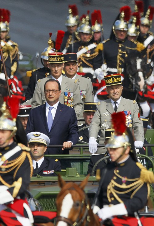 French President Francois Hollande stands at attention in the command car as he reviews the troops while descending from the Champs Elysees at the start of the traditional Bastille Day military parade in Paris