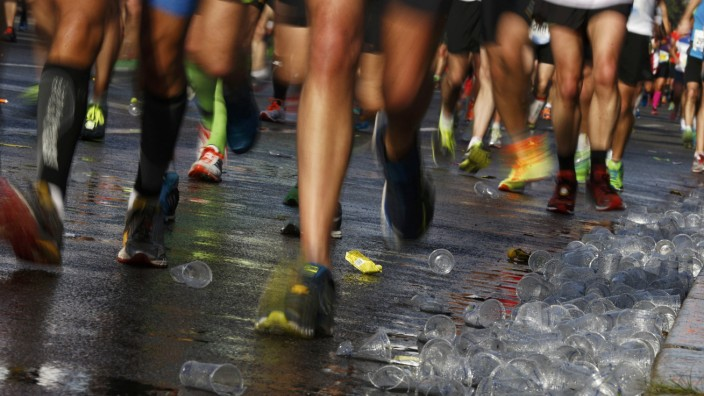Runners pass plastic cups on ground at a drinks station as they compete in the 41st Berlin marathon
