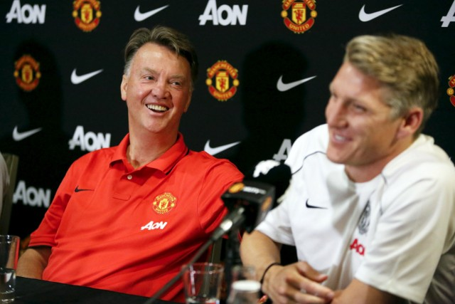 Manchester United's manager Louis van Gaal laughs as he and player Bastian Schweinsteiger speak to the media as the team introduces three new signings: Schweinsteiger, Morgan Schneiderlin and Matteo Darmian, at a news conference in Bellevue