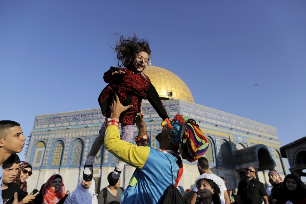 A man dressed as a clown plays with a Palestinian girl on the first day of the Muslim holiday of Eid al-Fitr, which marks the end of the holy month of Ramadan, in Jerusalem's Old City