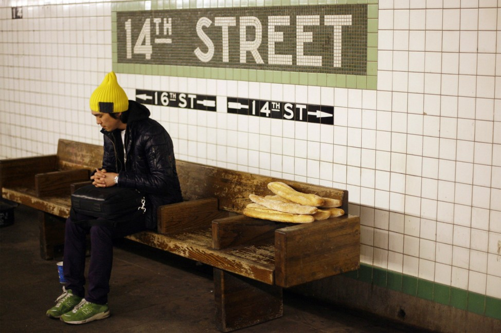 A man sits on a bench next to a pile of baguettes in a subway tunnel in New York