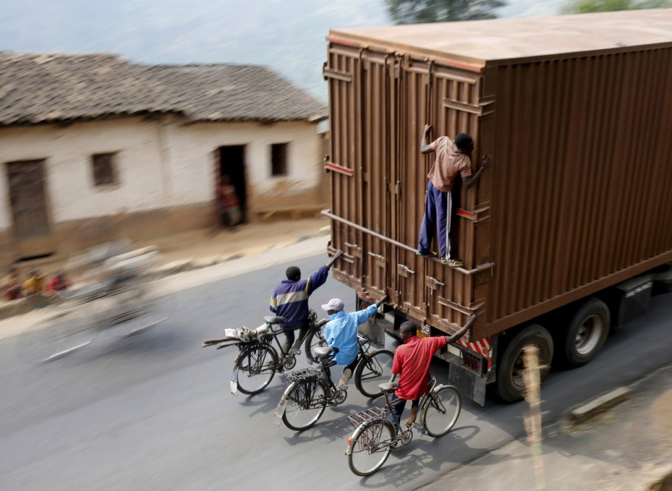 Cylists hang to the back of a truck outside the capital Bujumbura as the country awaits next week's presidential elections