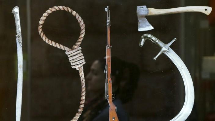 Die Werkzeuge des Völkermords, so arrangiert, dass sie die Zahl 1915 ergeben: Eine Frau spiegelt sich in Jerewan in einer der Plakatwände, die in der ganzen Stadt hängen.