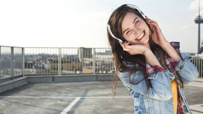 Germany North Rhine Westphalia Cologne portrait of laughing young woman listening music with head