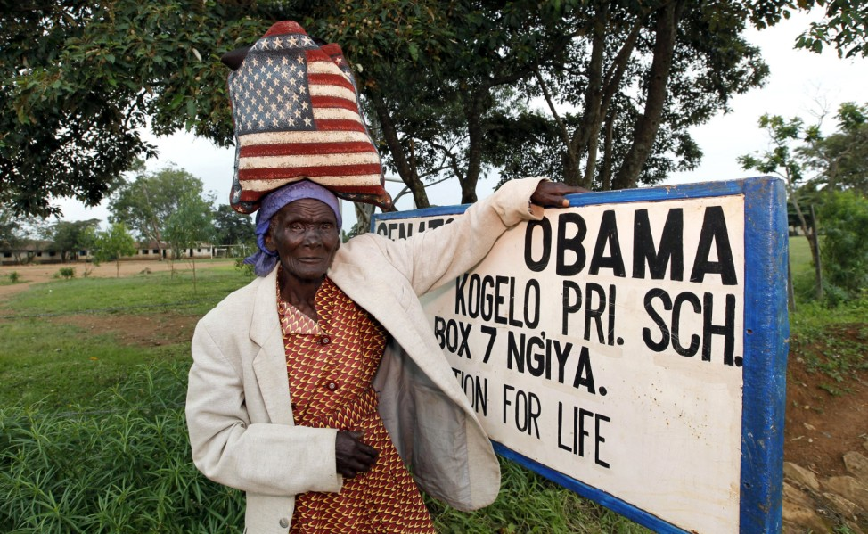 Rosa Anyango poses for a photograph as she carries a bag with the colors of the U.S. flag as she walks from the market near the ancestral home of U.S. President Barack Obama in Nyangoma village in Kogelo