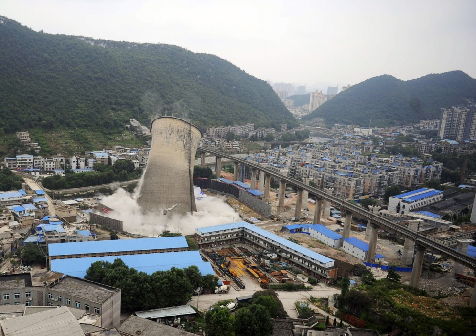 A cooling tower of a coal-burning power plant topples during a controlled demolition in Guiyang