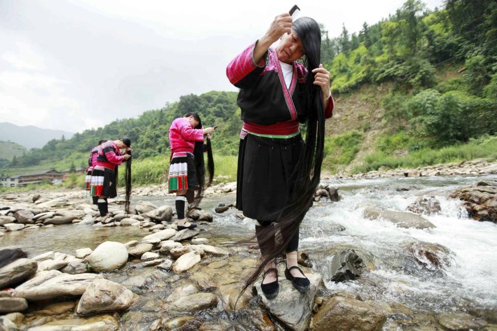 Ethnic Yao minority women brush their long hair near a creek, in Huangluo village of Guilin