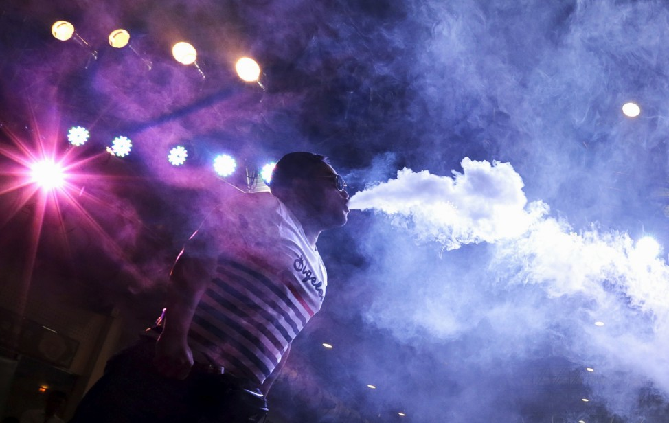 A participant puffs during a competition on the distance of the smoke being exhaled using an electronic cigarette at VAPE CHINA EXPO in Beijing
