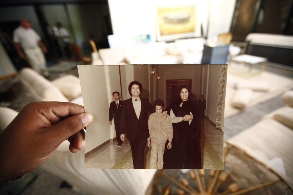 A Libyan shows a photograph of Gaddafi,his son Seif al Islam and his wife Safia at Hannibal's house in Tripoli