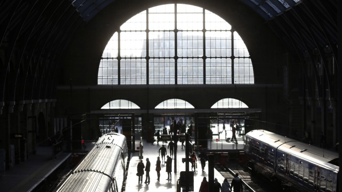 Passengers walk along a platform at King's Cross station in London