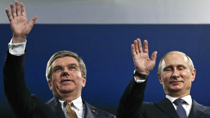 IOC President Bach and Russian President Putin wave during the closing ceremony for the 2014 Sochi Winter Olympics