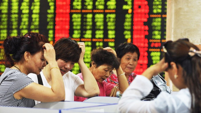 Investors react as they look at computer screens showing stock information at a brokerage house in Fuyang