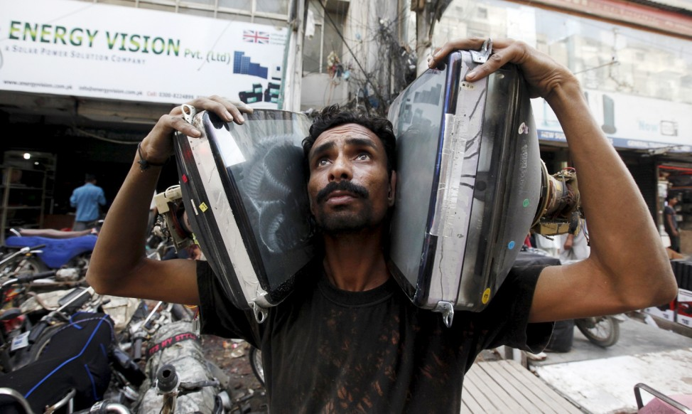 A man carries secondhand monitor picture tubes to install in homemade television sets at a market in Karachi, Pakistan