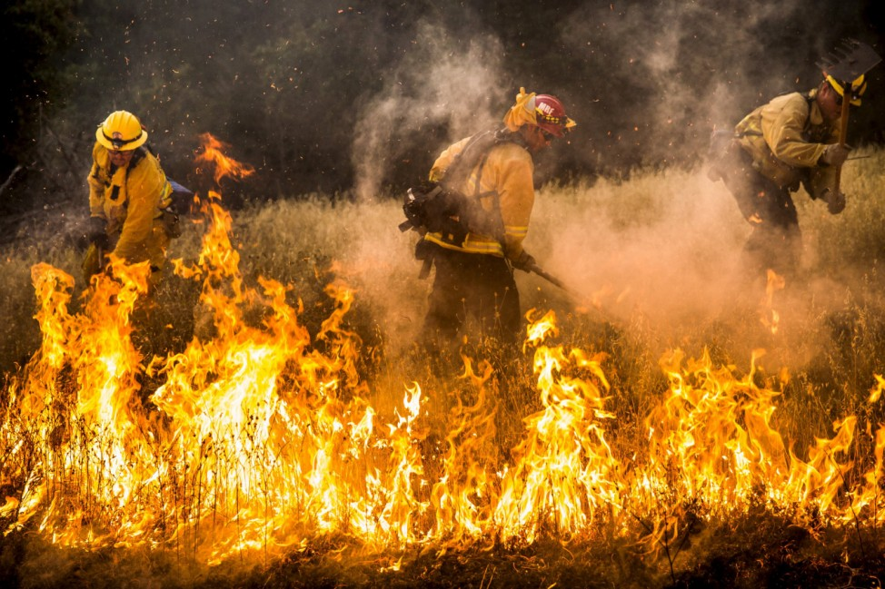 Firefighters work to dig a fire line on the Rocky Fire in Lake County, California