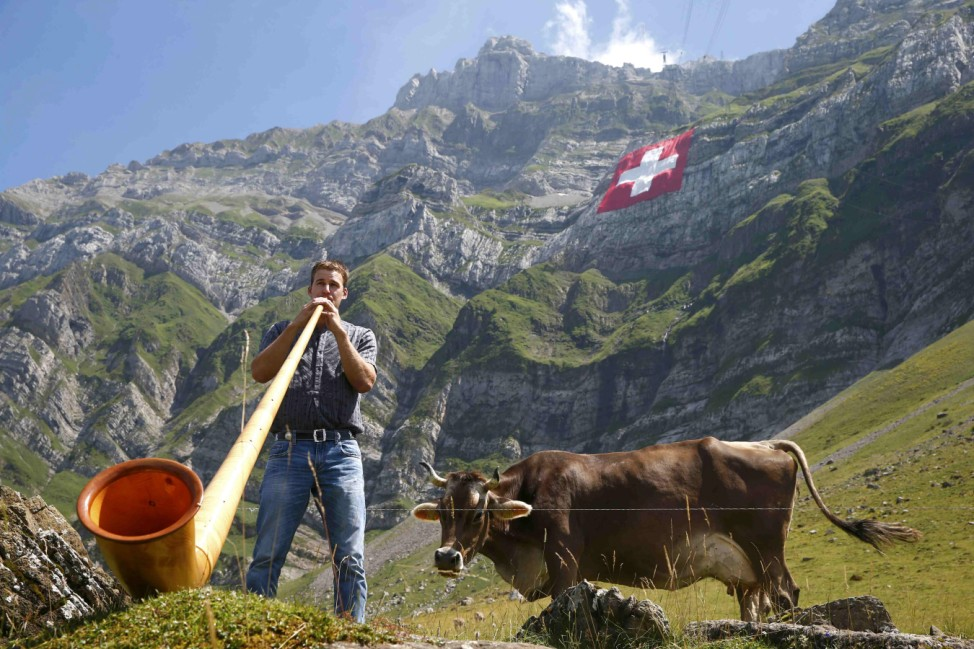 A man plays an alp horn as a huge 80x80 metres Swiss national flag is seen on the western face of the north-eastern Swiss landmark Mount Saentis