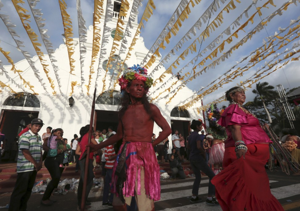 People dressed as Red Indian dance during celebrations honouring Santo Domingo de Guzman in Managua