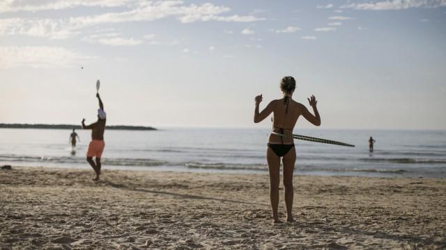 A woman spins a hula hoop around her waist on a beach in Tel Aviv