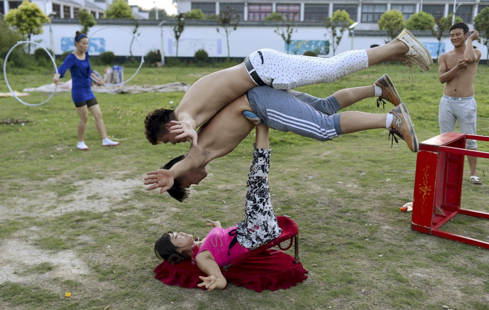 A woman balance two men with her feet as students practice at an acrobatic school in Sanwang village