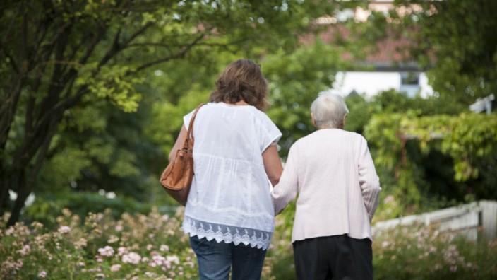 Soziales Engagement: Eine ehrenamtliche Helferin mit einer Seniorin beim Spaziergang.