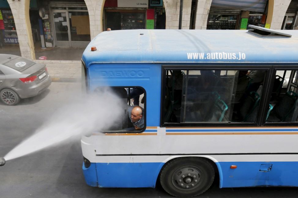 A bus driver reacts as Greater Amman Municipality personnel spray them with a water sprinkler in order to cool them down as part of measures to ease the effect of a heatwave, in Amman