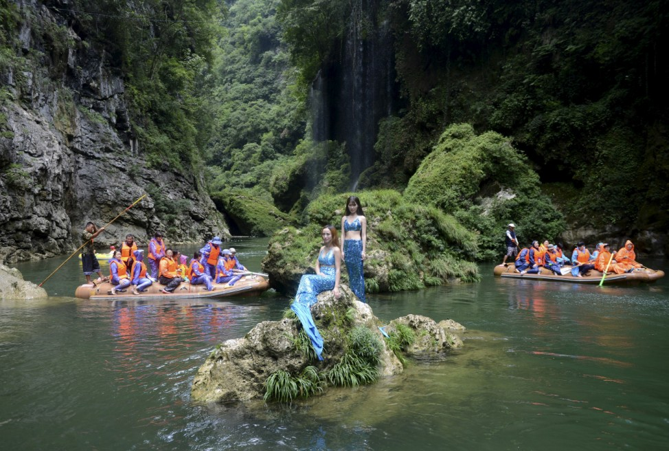 Tourists traveling on rafts look on as women dressed as mermaids pose for photographs in a river, as part of a promotional campaign at a tourism resort in Yongshun county