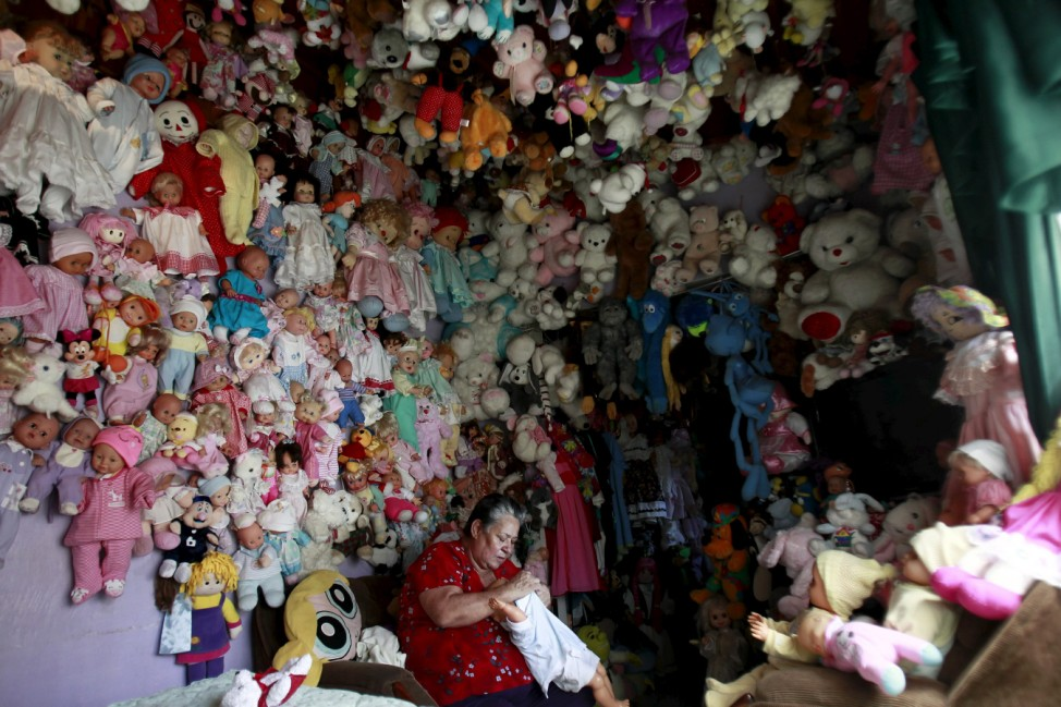 Adela Rojas changes the clothing of a doll at her home in Heredia