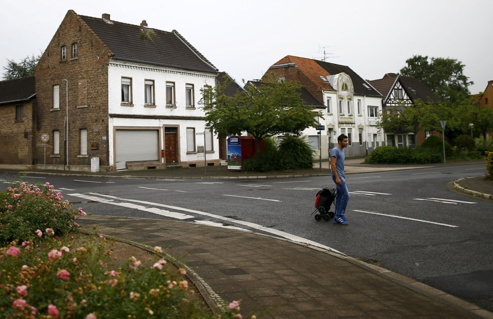 Alban, a 27-year old refugee from Albania walks through the empty streets of the village of Kerpen Manheim on their way towards the bus station in Manheim