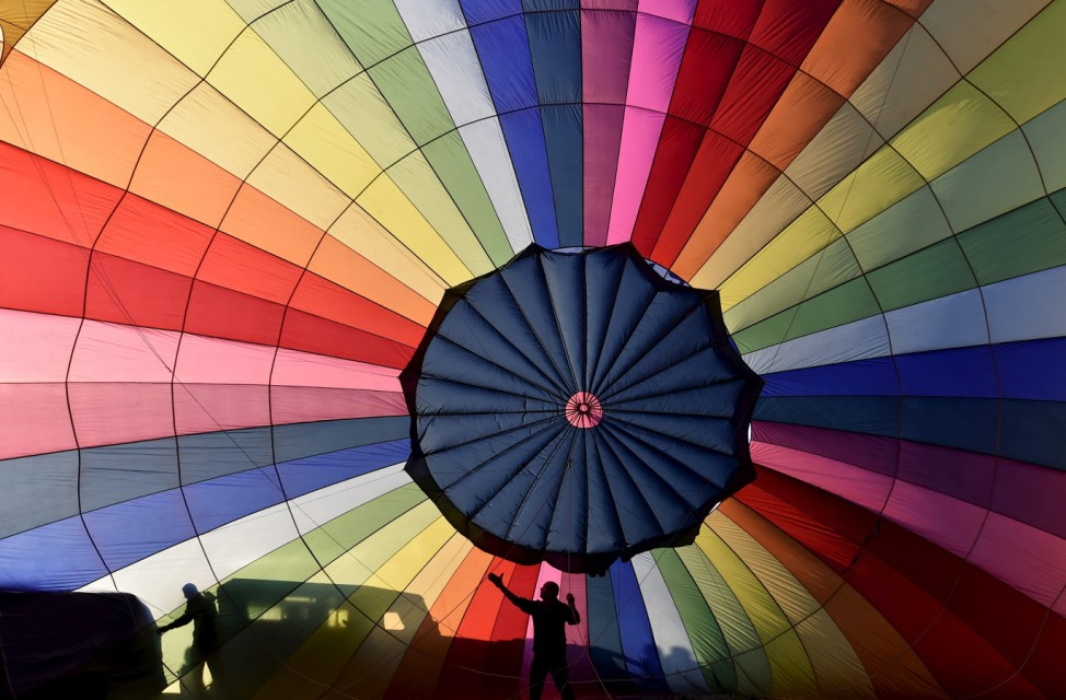 Crew members inflate a balloon during a mass launch at the Bristol International Balloon Fiesta in south west England
