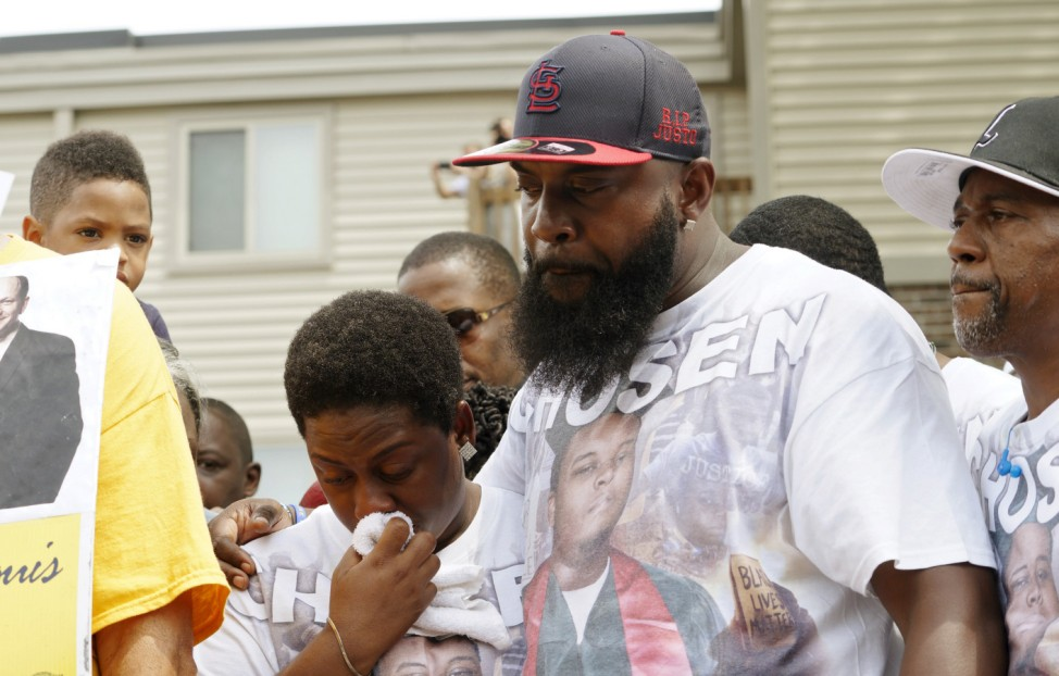 Michael Brown Sr., at the spot where his son was killed, comforts his wife Cal Brown during 4-1/2 minutes of silence to mark the one-year anniversary of the killing of his son Michael Brown in Ferguson