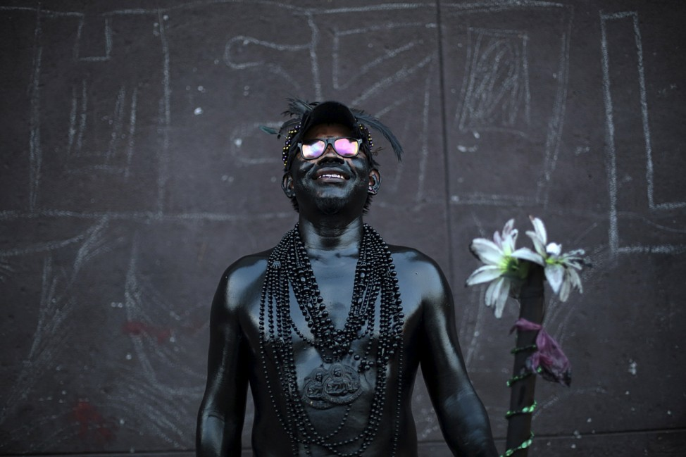 A devotee covered in motor oil poses for a pictures during celebrations honoring to Santo Domingo de Guzman in Managua