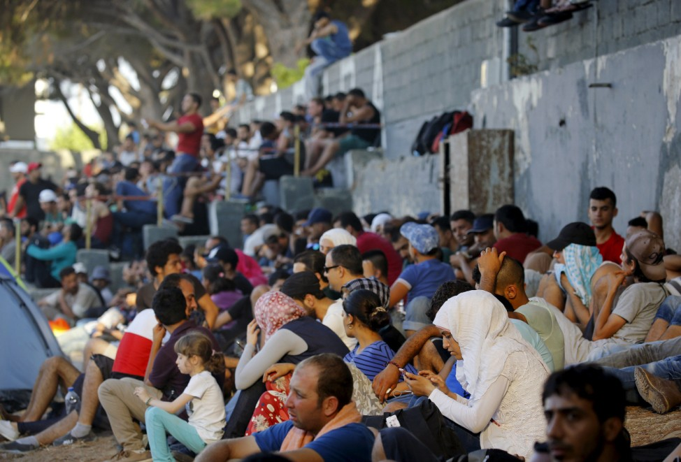 Syrian refugees pack the stands of the national stadium on the Greek island of Kos