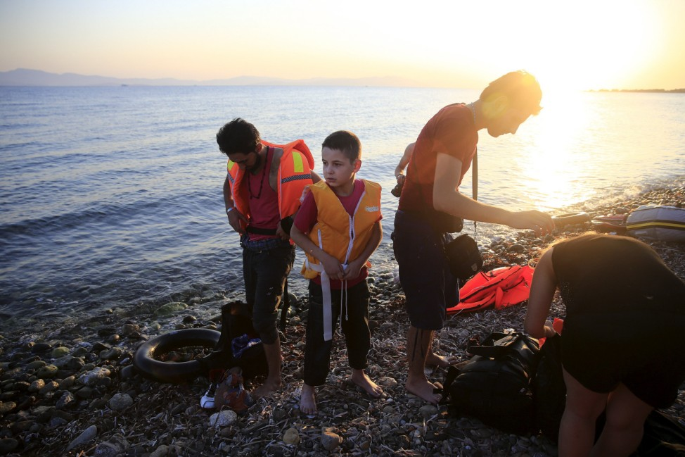 A migrant boy prepares to remove his life-jacket as others put dry clothes on moments after arriving at a beach on the Greek island of Kos