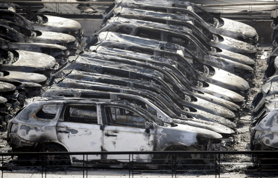 Damaged vehicles are seen near the site of the explosions at the Binhai new district, Tianjin