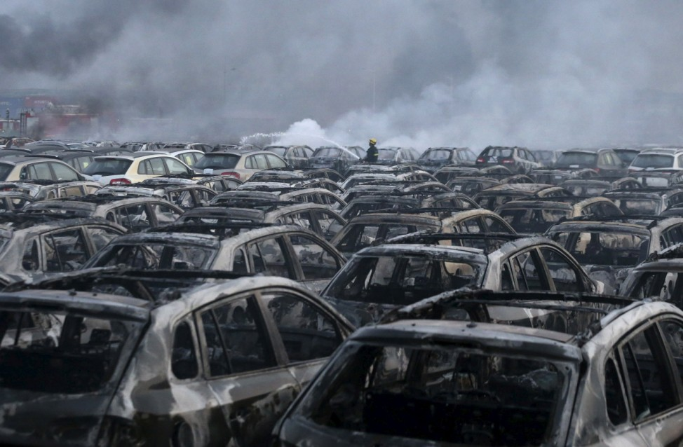 A firefighter works at the site near damaged vehicles as smoke rises from the debris after the explosions at the Binhai new district in Tianjin