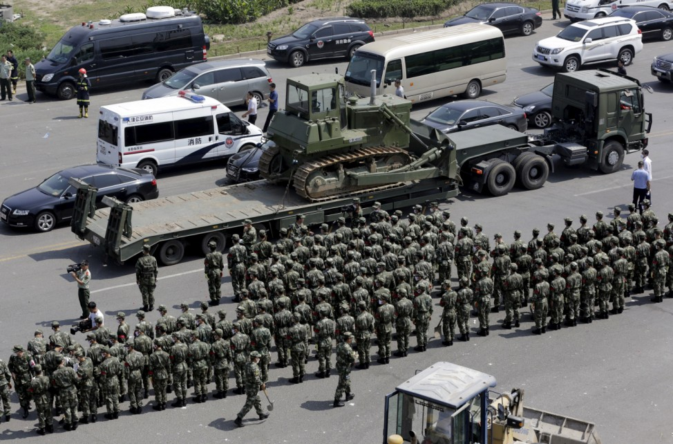 Paramilitary police stand in formation outside the site of the explosions at the Binhai new district