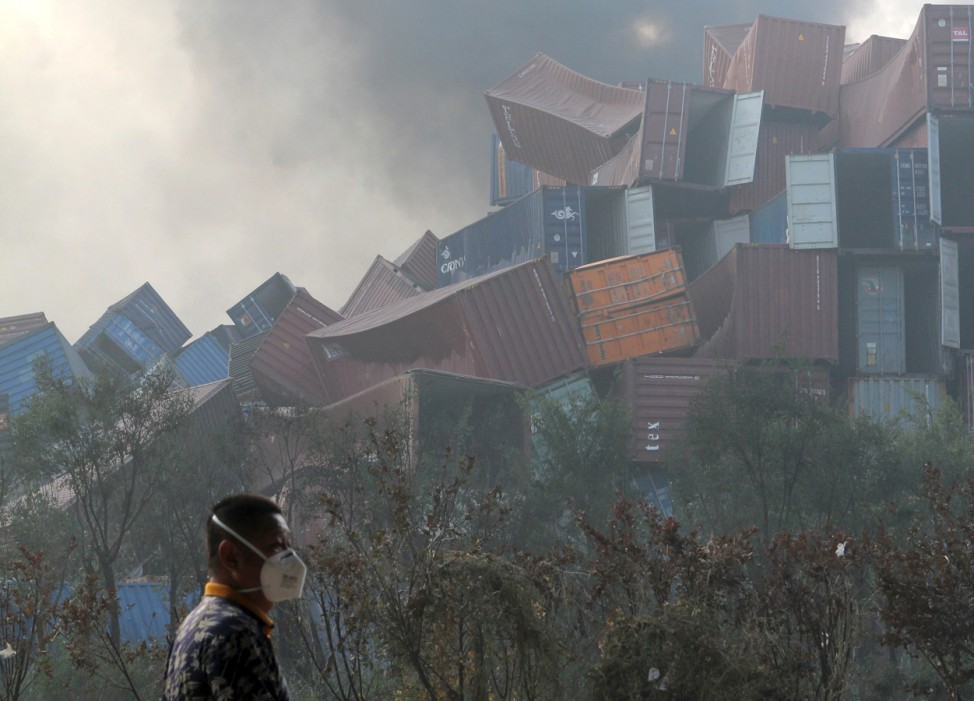A man wearing a mask walks past overturned shipping containers after explosions hit the Binhai new district in Tianjin