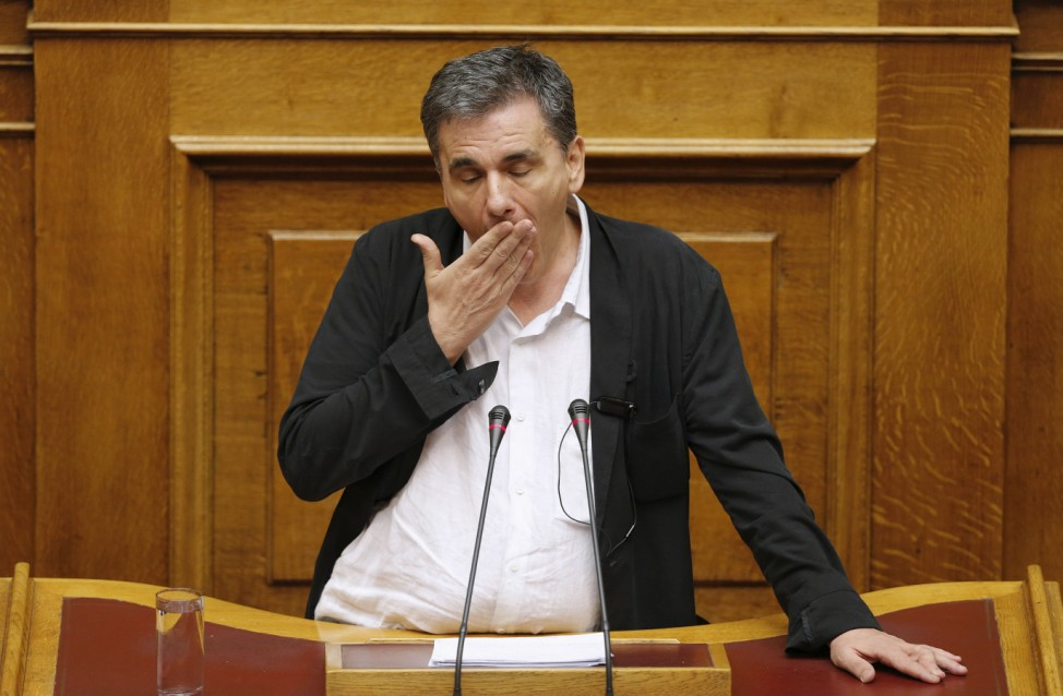 Greek Finance Minister Euclid Tsakalotos reacts as deputies attempt to disrupt his speech during a night parliamentary session in Athens