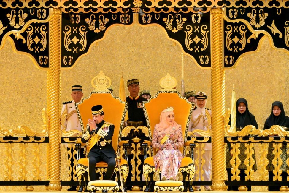 Brunei's Sultan Hassanal Bolkiah sits next to Queen Saleha during his 69th birthday celebration in Nurul Iman palace in Bandar Seri Begawan, Brunei
