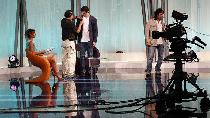 A microphone is put on Achilli before an interview at Italy's RAI television studios in Rome