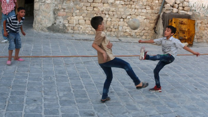 Children play football on a street in Aleppo