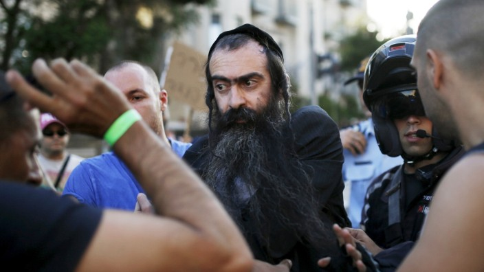 People detain after disarming an Orthodox Jewish assailant, after he stabbed and injured six participants of an annual gay pride parade in Jerusalem on Thursday, police and witnesses said; 2015-07-30T181039Z_1716008714_GF20000009109_RTRMADP_3_ISRAEL-GAY