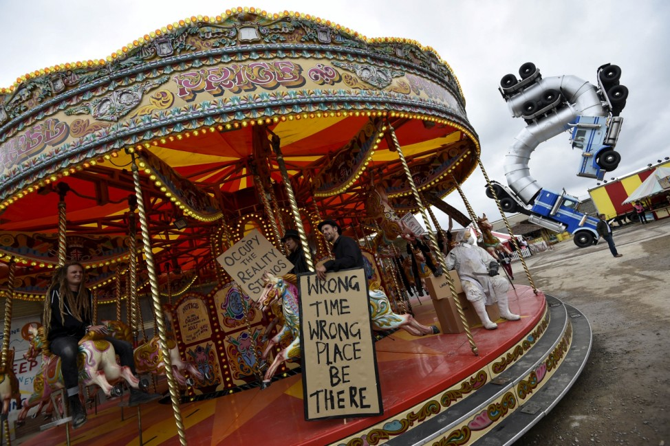 People ride a carousel at 'Dismaland', a theme park-styled art installation by British artist Banksy, at Weston-Super-Mare in southwest England