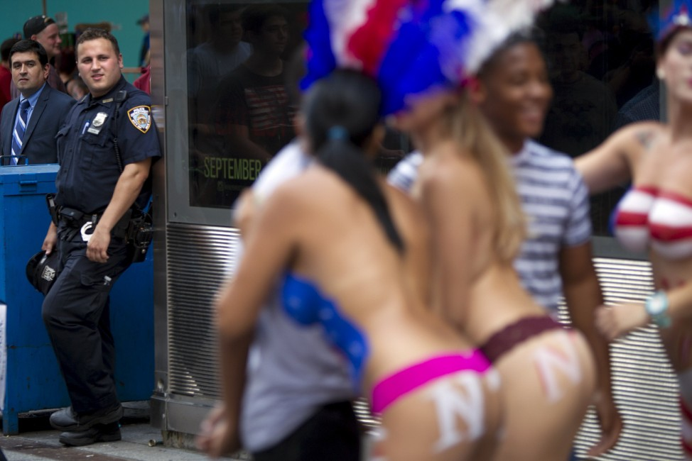 A policeman looks on as women who pose for tips wearing body paint and underwear are pictured in Times Square in New York