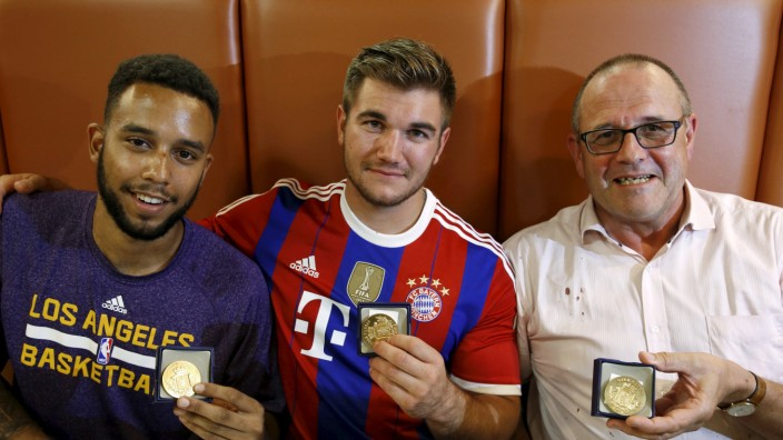 Sadler, Sharlatos, and Norman, three men who helped to disarm an attacker on a train from Amsterdam to France, pose with their medals at a restaurant in Arras, France