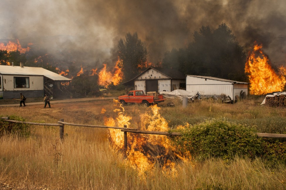 Firefighters attempt to protect a home and outbuildings from the Twisp River fire near Twisp, Washington