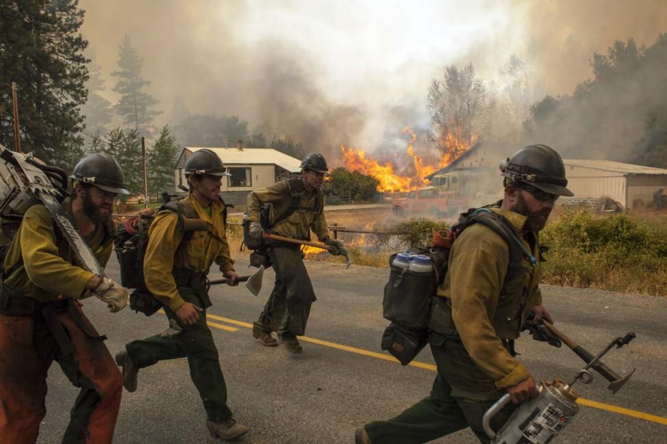 Firefighters flee as the Twisp River fire advances unexpectedly near Twisp, Washington